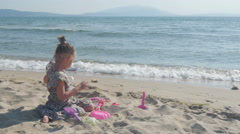 Cute female child playing with toys on sand beach near the wavy sea by Sheyno. Stock Footage