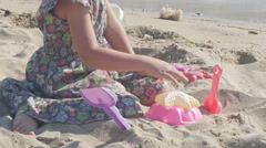 Little girl playing in sand with toys by Sheyno, tilt up from hands to face. Stock Footage