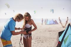 Man fastening kiteboarding safety harness onto woman on sunny beach - stock photo