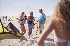 Friends learning to kiteboard on sunny beach - stock photo