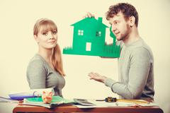 Young couple with ecological green house. - stock photo