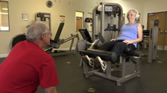 Mature Man Coaching Woman In Leg Exercise At Fitness Center Stock Footage