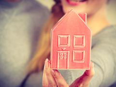 People together with house model. - stock photo