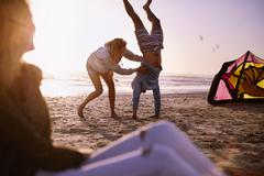 Woman holding man doing handstand on sunset beach - stock photo