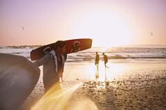Man carrying kiteboard on sunset beach - stock photo