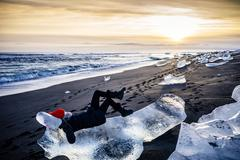 Woman laying on large ice chunk on beach at sunset, Iceland Stock Photos