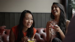 4K Happy mixed ethnicity group of friends chatting over drinks in city bar Stock Footage