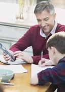 Father with calculator helping son doing math homework Stock Photos
