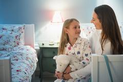Mother and daughter talking at bedtime in bedroom Stock Photos