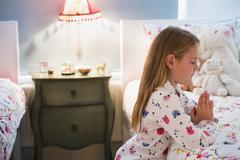 Girl in pajamas saying bedtime prayers at bed Stock Photos
