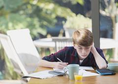 Boy doing math homework at dining table Stock Photos