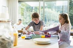 Brother and sister eating breakfast and doing homework Stock Photos
