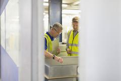 Supervisor and worker inspecting pieces in steel factory Stock Photos