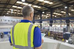 Supervisor with clipboard in steel factory Stock Photos