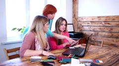 Three girls discuss plans for a sheet of paper in the office designers Stock Footage