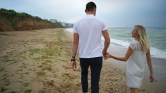 back view romantic walk of young couple on the beach slow motion - stock footage