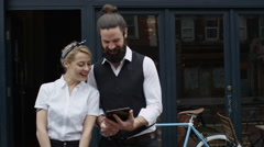 4K Portrait smiling cafe owners standing outside shop with computer tablet Stock Footage