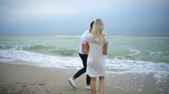 Young couple throwing rocks into the stormy sea slow motion Stock Footage