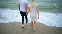Back view young couple running away of wave at the sea edge slow motion Stock Footage
