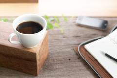 white cup coffee with note book smart phone on wooden top table - stock photo