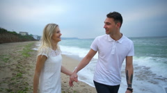Romantic couple walk along the sea and kiss slow motion Stock Footage