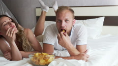 The girl and the guy eating chips lying on the bed Stock Footage