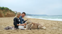 young couple relaxing on the beach with husky dog slow motion - stock footage