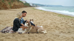 Young couple relaxing on the beach with husky dog slow motion Stock Footage