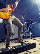 Rock and roll guitar player on stage - stock photo