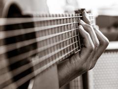 Closeup of playing an acoustic guitar Stock Photos