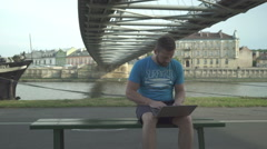 Man is browsing laptop, sitting on bench against the river, steadicam Stock Footage
