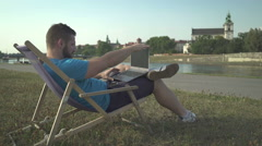 Man ends typing on laptop and chilling out on sunbed by the river. - stock footage