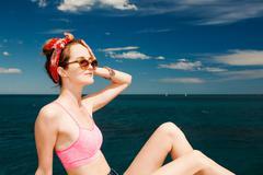 Attractive girl model in sunglasses sunbathing on beach Stock Photos