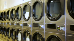 Teenage boy doing the laundry in a public laundromat. Stock Footage