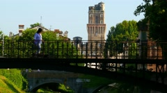 Padua - Walking on iron bridge and the Specola in background Stock Footage