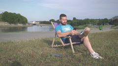 Man is browsing smartphone, lying on sunbed by the river. Stock Footage