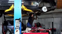 Repairman repairing exhaust system on lifted up sedan car in car repair shop Stock Footage