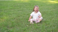 Children crying on green grass background, Small baby girl spending time outdoor Stock Footage