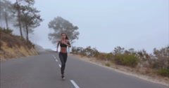 Fitness woman sprinting on countryside highway Stock Footage