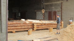 Man raises a wooden beam on the crane in a hangar. Work makes a wooden cottage Stock Footage
