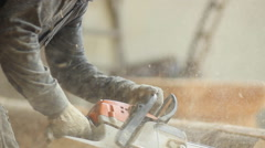 Man working with a chainsaw. Wood shavings are flying saw his face. Close up Stock Footage