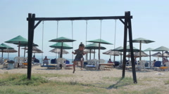 Cute female child swinging on the sand beach with reed umbrellas by Sheyno. Stock Footage