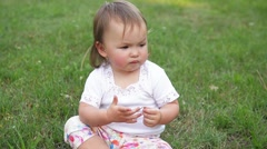 Crying little child in a park, cute girl sadly spending time outdoor Stock Footage