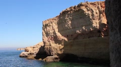 A man can just be seen walking high above on the clifftops of the Algarve coast. Stock Footage