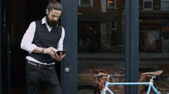 4K Smiling bar or cafe owner standing outside shop with computer tablet. Stock Footage