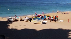 Men prepare colorful boats on beach at the edge of the Atlantic ocean Stock Footage