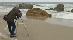 Photographer adjusts camera on tripod on sand beach near rocks and stormy sea. Stock Footage