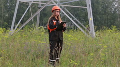 Woman engineer working near an electrical substation lines, power lines,teamwork Stock Footage