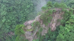 CINEMATIC AERIAL POI SHOT OF TOURISTS STANDING ON STEEP CLIFF SIDE ZHANGJIAJIE Stock Footage