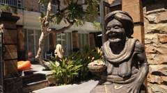Statue of a smiling balinese grandma in front of a hotel Stock Footage
